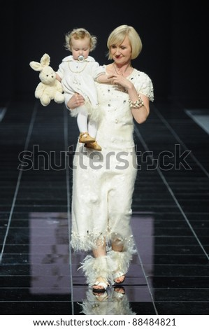 MOSCOW - OCTOBER 27: Model walks the runway with baby on hands at the Anna Lesnikova Collection for Spring/ Summer 2012 during Volvo Fashion Week on October 27, 2011 in Moscow, Russia