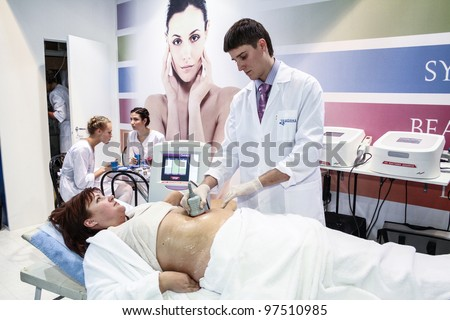 MOSCOW - OCTOBER 26: Procedure of vacuum massage at the international exhibition of professional cosmetics and beauty salon equipment INTERCHARM on October 26, 2011 in Moscow - stock photo