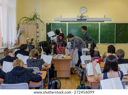 MOSCOW OCTOBER 3 - Unidentified students of the senior class substitute teacher and independently teach a lesson of mathematics in the Junior class. Teachers' Day in Moscow school October 3, 2014 - stock photo