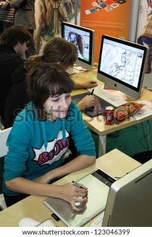 MOSCOW- OCTOBER 7:  Unidentified young girl artist draws a digital pen at the international exhibition of  the entertainment industry, Igromir on October 7, 2012 in Moscow - stock photo