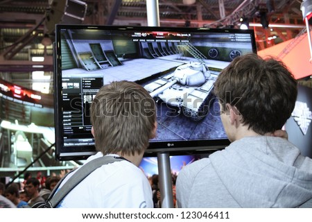 MOSCOW- OCTOBER 7:  Unidentified young people playing video games at the international exhibition of  the entertainment industry, Igromir on October 7, 2012 in Moscow - stock photo
