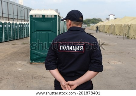 MOSCOW, RUSSIA - AUGUST 1, 2013:  Temporary camp for displaced persons contains illegal migrants from Asian countries, discovered during police raids, pending deportation to their homeland.