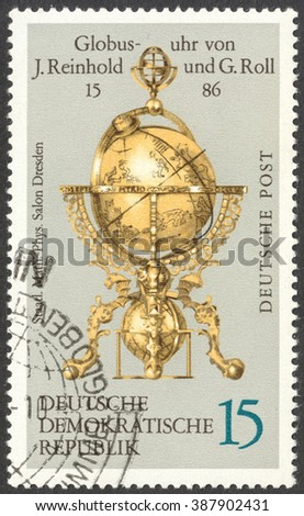 "MOSCOW, RUSSIA - CIRCA FEBRUARY, 2016: a post stamp printed in DDR shows  globe clock by Reinhold and Georg Roll, the series ""Globes"", circa 1972 - stock photo"