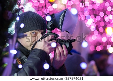 MOSCOW, RUSSIA - DECEMBER 24, 2016: Photographer at work, Snow Maidens Parade at Pushkin Square - a part of Journey to Christmas Festival