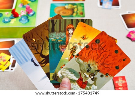 MOSCOW, RUSSIA - FEBRUARY 3, 2014: Dixit game cards in hand. The game was created by Jean-Louis Roubira in 2008, and in 2010 the game received prestigious award Spiel des Jahres (Game of the Year) - stock photo
