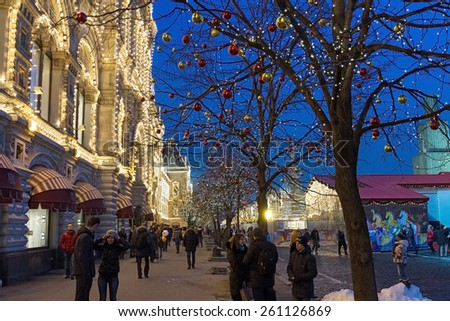 Moscow , Russia - February 21, 2015 : Illuminated GUM and Christmas market in holiday decoration on the Red Square . People walk on the Red Square and the sidewalk . Moscow, Russia. - stock photo