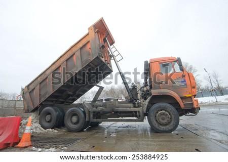 MOSCOW, RUSSIA - February 13, 2015: Orange dump truck KAMAZ pours snow in negotable on snow-melting point, Moscow