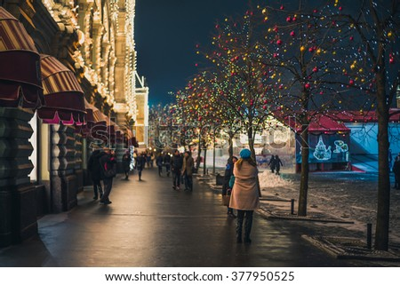 MOSCOW, RUSSIA - FEBRUARY 14, 2016. Tourists walking on Red Square along the State Department Store in the evening. Focus on the woman in the foreground, the background is out of focus. - stock photo