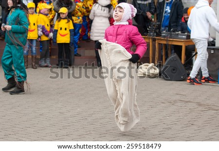 MOSCOW, RUSSIA - FEBRUARY 22: Unidentified girl run in sack on Russian religious and folk holiday Maslenitsa near Culture center Peresvet on February 22, 2015, Russia - stock photo
