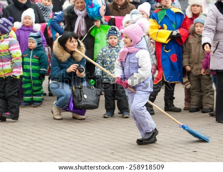 MOSCOW, RUSSIA - FEBRUARY 22: Unidentified girl run on broom on Russian religious and folk holiday Maslenitsa near Culture center Peresvet on February 22, 2015, Russia - stock photo