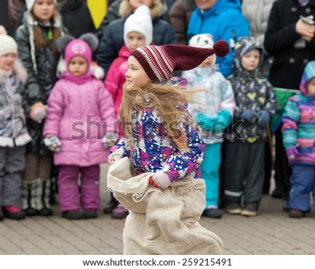 MOSCOW, RUSSIA - FEBRUARY 22: Unidentified girl running on Russian religious and folk holiday Maslenitsa near Culture center Peresvet on February 22, 2015, Russia - stock photo