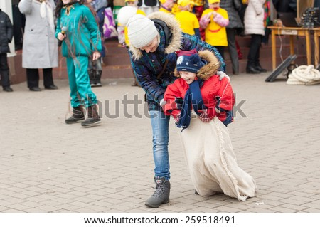 MOSCOW, RUSSIA - FEBRUARY 22: Unidentified woman helps to run in sack on Russian religious and folk holiday Maslenitsa near Culture center Peresvet on February 22, 2015, Russia - stock photo