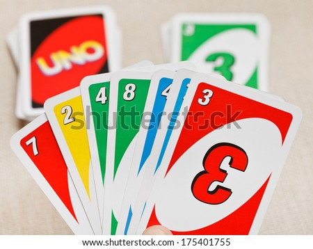 MOSCOW, RUSSIA - FEBRUARY 3, 2014: view of Uno card game pack in hand. The game was developed by Merle Robbins in USA in 1971, and it has been Mattel product since 1992 - stock photo