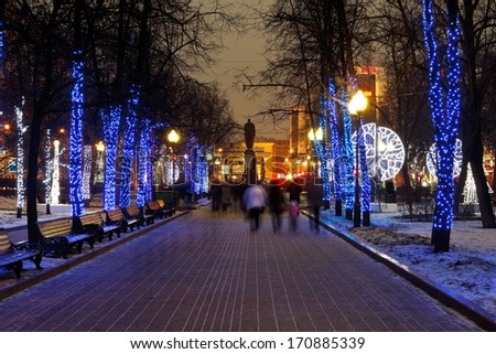 MOSCOW, RUSSIA - JANUARY 3, 2014: people walking on Moscow Clear Ponds boulevard with christmas night illumination. More than 4 thousand trees in urban center were decorated with garlands - stock photo