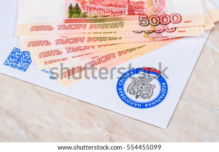 MOSCOW, RUSSIA - JANUARY 9, 2017: Tax payment notice letter with logo of the Federal Tax Service of Russia and ruble banknotes above. Tax payment concept
