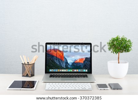 Moscow, Russia - January 31, 2016: Workplace with modern gadgets iPhone 6, ipad and Macbook pro by Apple. Apple is an American corporation that designs, develops, and sells consumer electronics - stock photo