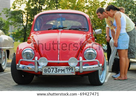 MOSCOW,RUSSIA-JULY 31: Two unidentified person look in red vintage Volkswagen Beetle  in exhibition parking show of retro-cars 'Night Moscow Classic Rally-2010' on July 31, 2010 in Moscow, Russia - stock photo