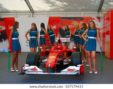 MOSCOW, RUSSIA - JULY 14: Young ladies posing at red car exponent at Moscow City Racing. Formula 1 teams show in historical city center of Moscow. Taken on July 14, 2012 in Moscow, Russia. - stock photo