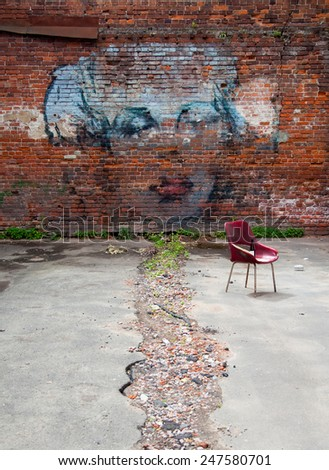 MOSCOW, RUSSIA -JUNE 22, 2014: Brick wall covered by graffiti of Marilyn Monroe's portrait in Moscow courtyard - stock photo