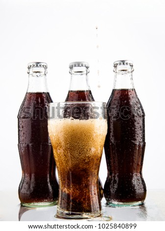 MOSCOW, RUSSIA - JUNE 22, 2012: Coke, glass, wet.Three Coke glass bottles, isolated on white background. Illustrative Editorial. plastic bottle above