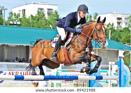 MOSCOW, RUSSIA-JUNE 26: Rider Tuganov Vladimir (RUS) with a Holsten horse Amarok competes at the International event CSI4*RR/ Russian Championship Show Jumping on June 26, 2011 in Moscow, Russia - stock photo