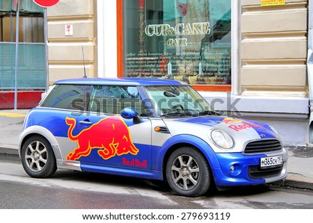 MOSCOW, RUSSIA - JUNE 3, 2012: Small car Autin Mini Cooper covered with the Red Bull advertisement at the city street. - stock photo