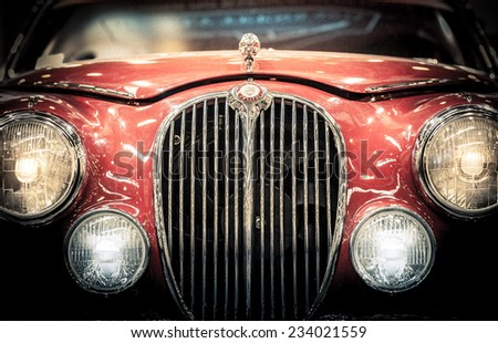 Moscow, Russia - March 3, 2013: Front headlights and grille of a restored red vintage Jaguar motor car showing the badge and hood ornament, close up frontal. - stock photo