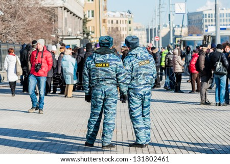 MOSCOW, RUSSIA - 8 MARCH: Policemen look at activists on picket to free Pussy Riot members on March 8, 2013 in Moscow.