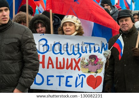 MOSCOW, RUSSIA - MARCH 2: Russian demonstrators with poster read 'Let's protect our children' on rally in support of U.S. adoption ban. Moscow, March 2, 2013