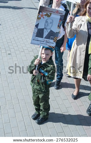MOSCOW, RUSSIA - MAY 09, 2014: A little boy wearing soldier's uniform holds portrait of his grandfather who fought in WWII.  March of 'Immortal Regiment' - stock photo