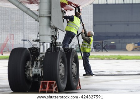 MOSCOW, RUSSIA - MAY 19, 2016: Aircraft  Tu-204 Red Wings airline in the parking lot of the airport Domodedovo. Service engineers carried out work on the preparation of the aircraft for the flight. - stock photo