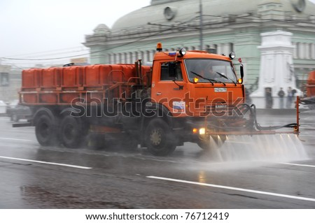 MOSCOW, RUSSIA - MAY 07: Big orange street cleansing machine washes the asphalt road  May 07, 2011 in Moscow, Russia. - stock photo