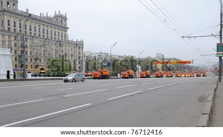 MOSCOW, RUSSIA - MAY 07: Big orange street cleansing machines wash the asphalt road before the Victory day military Parade May 07, 2011 in Moscow, Russia. - stock photo