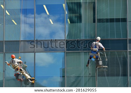 MOSCOW, RUSSIA - MAY 25, 2015: Group of workers cleaning windows service of  modern office building in Moscow International Business Center - stock photo