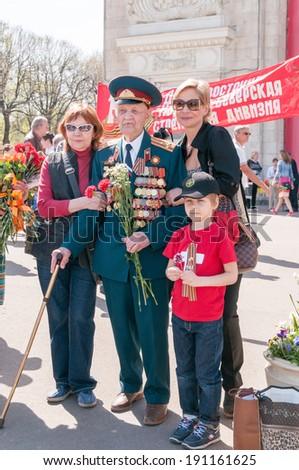 MOSCOW/RUSSIA - MAY 9: Old man veteran of WWII in uniform decorated with numerous orders and medals stands with Gorky Park visitors for common photo in Victory Day on May 9, 2013 in Moscow. - stock photo