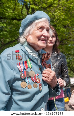 MOSCOW/RUSSIA - MAY 9: Old woman veteran of WWII in blue coat decorated with numerous orders and medals  during festivities devoted to anniversary of Victory Day on May 9, 2011 in Moscow. - stock photo