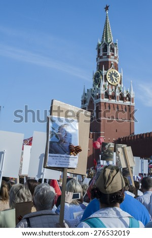 MOSCOW, RUSSIA - MAY 09, 2014:  People with portraits of their relatives during march of 'Immortal Regiment' in Moscow to honor relatives who fought in WWII. The vast column reached Red Square - stock photo