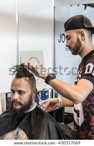 Moscow, Russia - May 27, 2016: The 8th Moscow International Tattoo Convention. Barber makes a man a haircut at the exhibition. focus on the client's face - stock photo