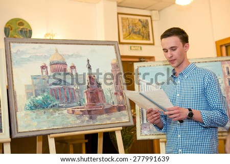 MOSCOW, RUSSIA, MAY 19, 2014: Unidentified teenager boy graduating the art school with his diploma painting works, May 19, 2014. - stock photo