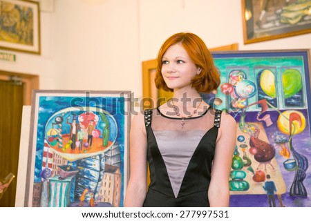 MOSCOW, RUSSIA, MAY 19, 2014: Unidentified teenager girl graduating the art school with his diploma painting works, May 19, 2014. - stock photo