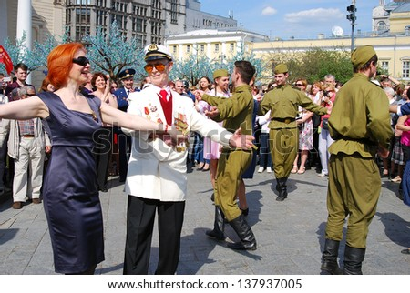 MOSCOW, RUSSIA - MAY 09: War veteran dances together with young actors dressed as army soldiers on the Theater Square, by the Bolshoi Theater. Victory Day celebration on May 09, 2013 in Moscow.