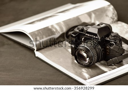 Moscow, Russia - October 25, 2013: Vintage mechanical 35mm film photo camera Pentax LX and photo book with monochrome picture. Toned image. - stock photo