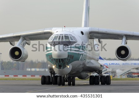 MOSCOW, RUSSIA - SEPTEMBER 26, 2014: Cargo airplane IL-76TD Alrosa airlines taxiing to the parking lot with the help of airport Marshal, - stock photo