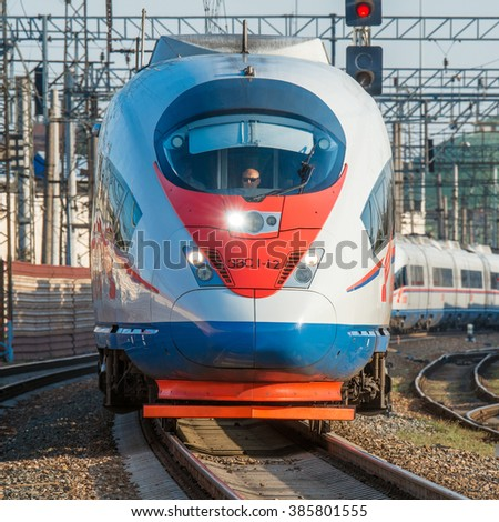 Moscow, Russia - September 19, 2015: Modern high-speed train moves from the station after departure at sunset time. - stock photo