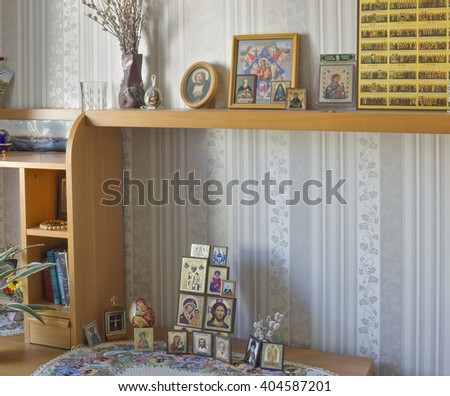 MOSCOW, RUSSIA - SEPTEMBER 16, 2015: Simple standard icons, photos of relatives and religious books in the room of the believing orthodox woman.  - stock photo