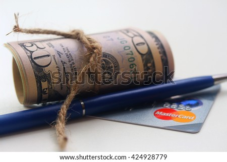 MOSCOW, RUSSIAN FEDERATION - MAY 19, 2016: parcel of dollars and MasterCard card - stock photo