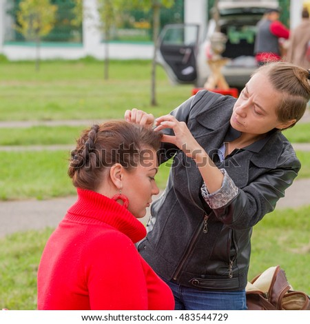 MOSCOW, RUSSIAN FEDERATION - SEPTEMBER 10, 2016: Model is preparing for the fashion show of Slavic clothing. Make-up artist creates an individual image with makeup. Park in Yasenevo.