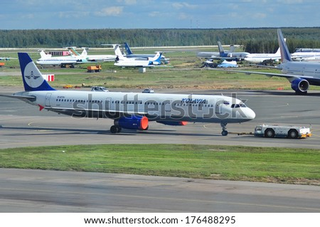 MOSCOW - SEPTEMBER 05: Airplane being towed at an airport Domodedovo in September 05, 2012 in Moscow. The airplane Airbus A321-231 of airline Kolavia Reg EI-ETH  - stock photo