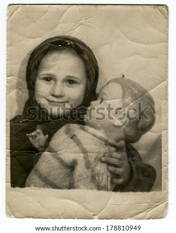"MOSCOW, USSR - CIRCA 1940s : An antique photo shows a little girl and a doll in her hands. ""Soviet people"" series."
