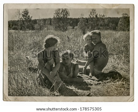 "MOSCOW, USSR - CIRCA 1970s : An antique photo shows family resting on the meadow. ""Soviet people"" series"